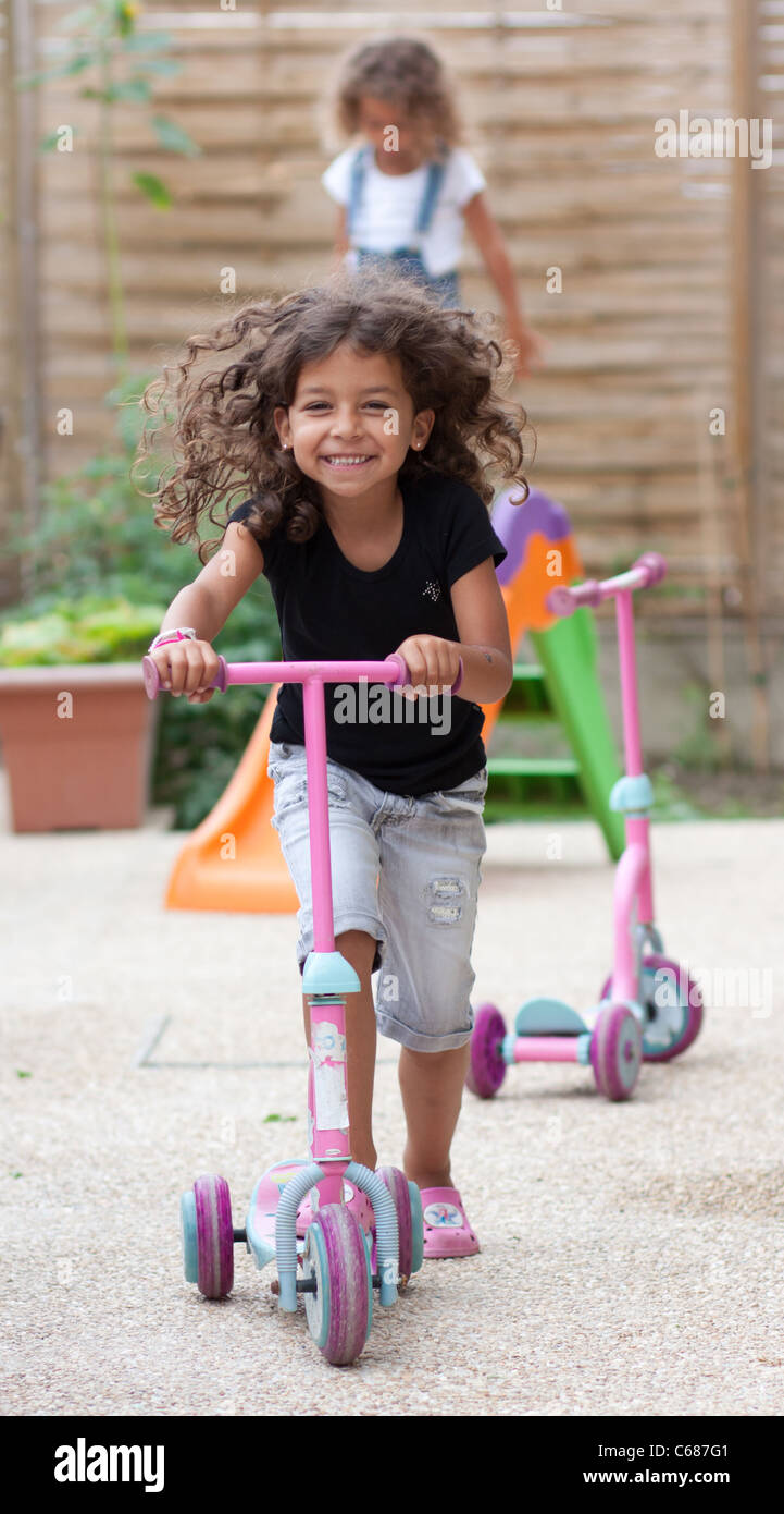 Smiling girl playing with a scooter - Stock Image