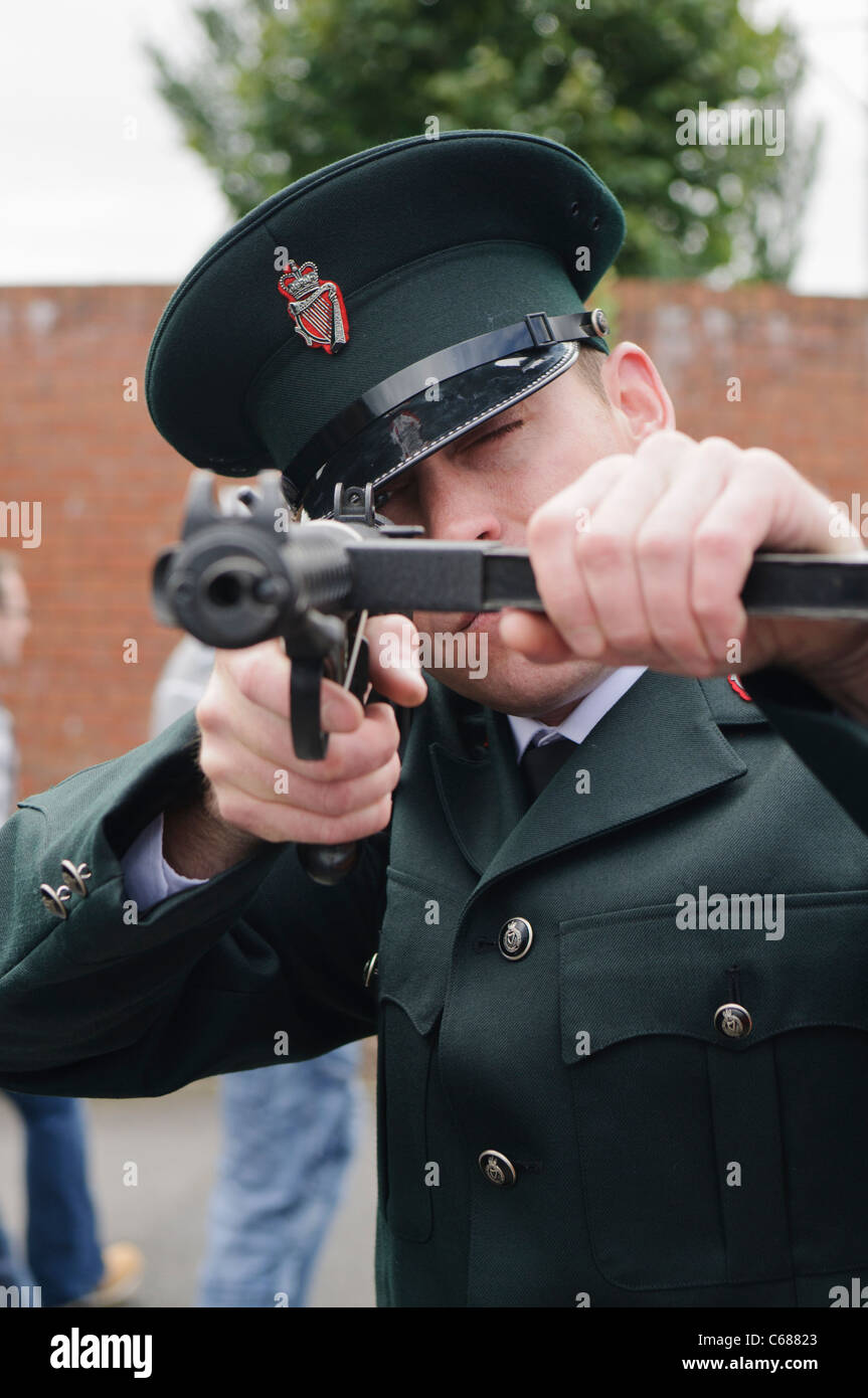 Man dressed in RUC police uniform, pointing a Sterling Machine Gun - Stock Image