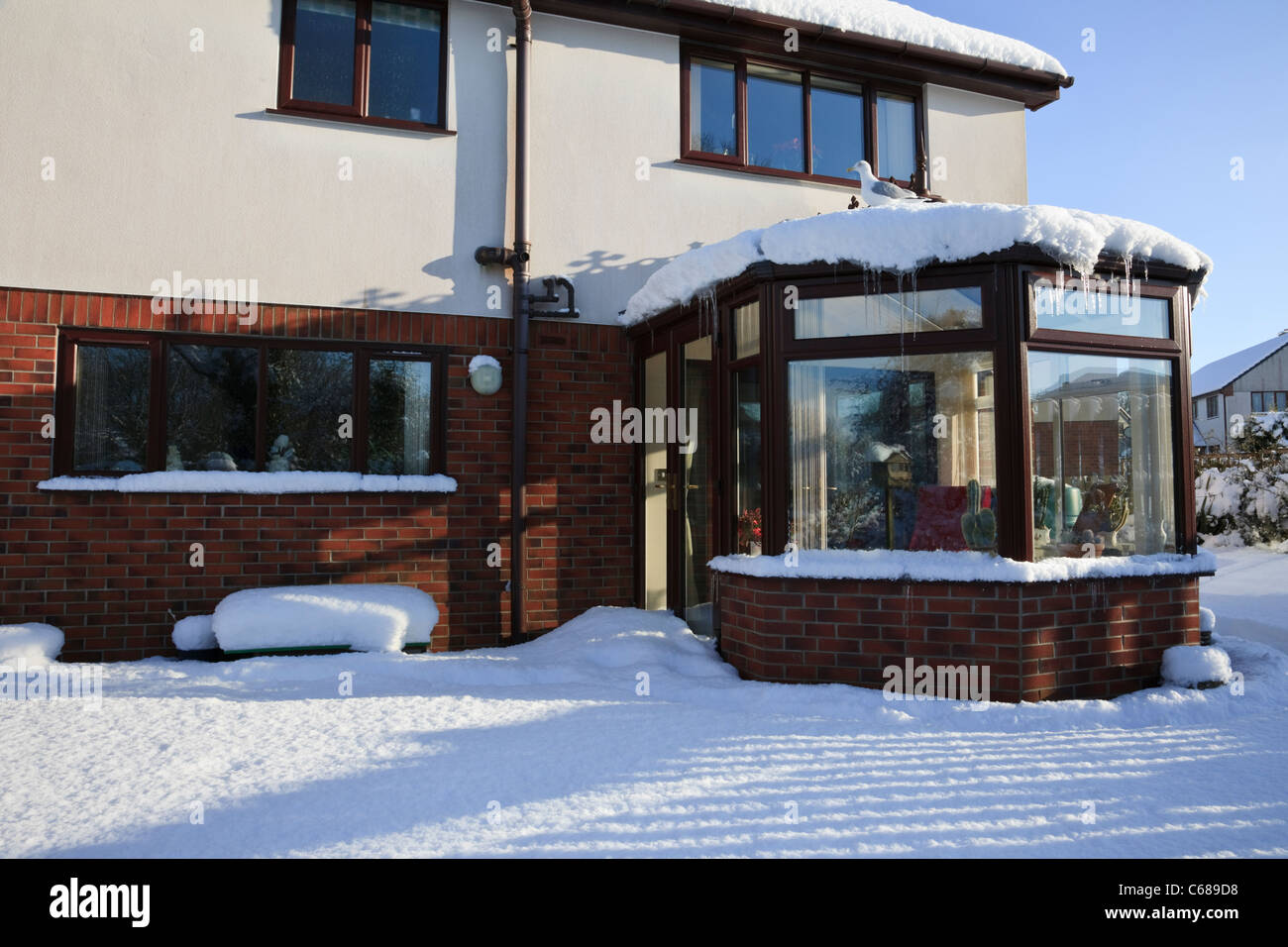 House with conservatory from back garden covered in snow in winter 2010. UK - Stock Image