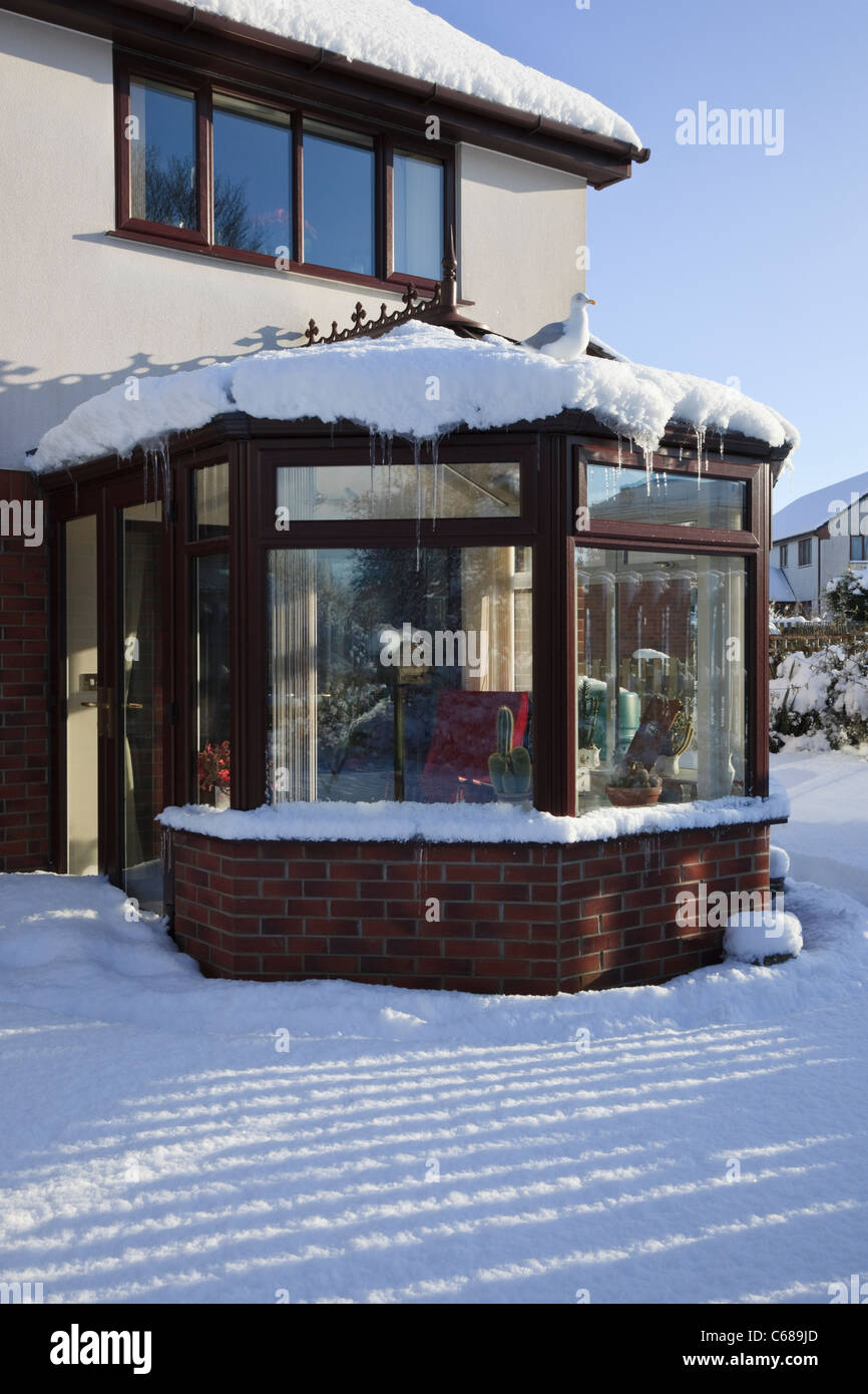 House and conservatory with icicles hanging down, from back garden covered in snow in winter 2010. UK - Stock Image