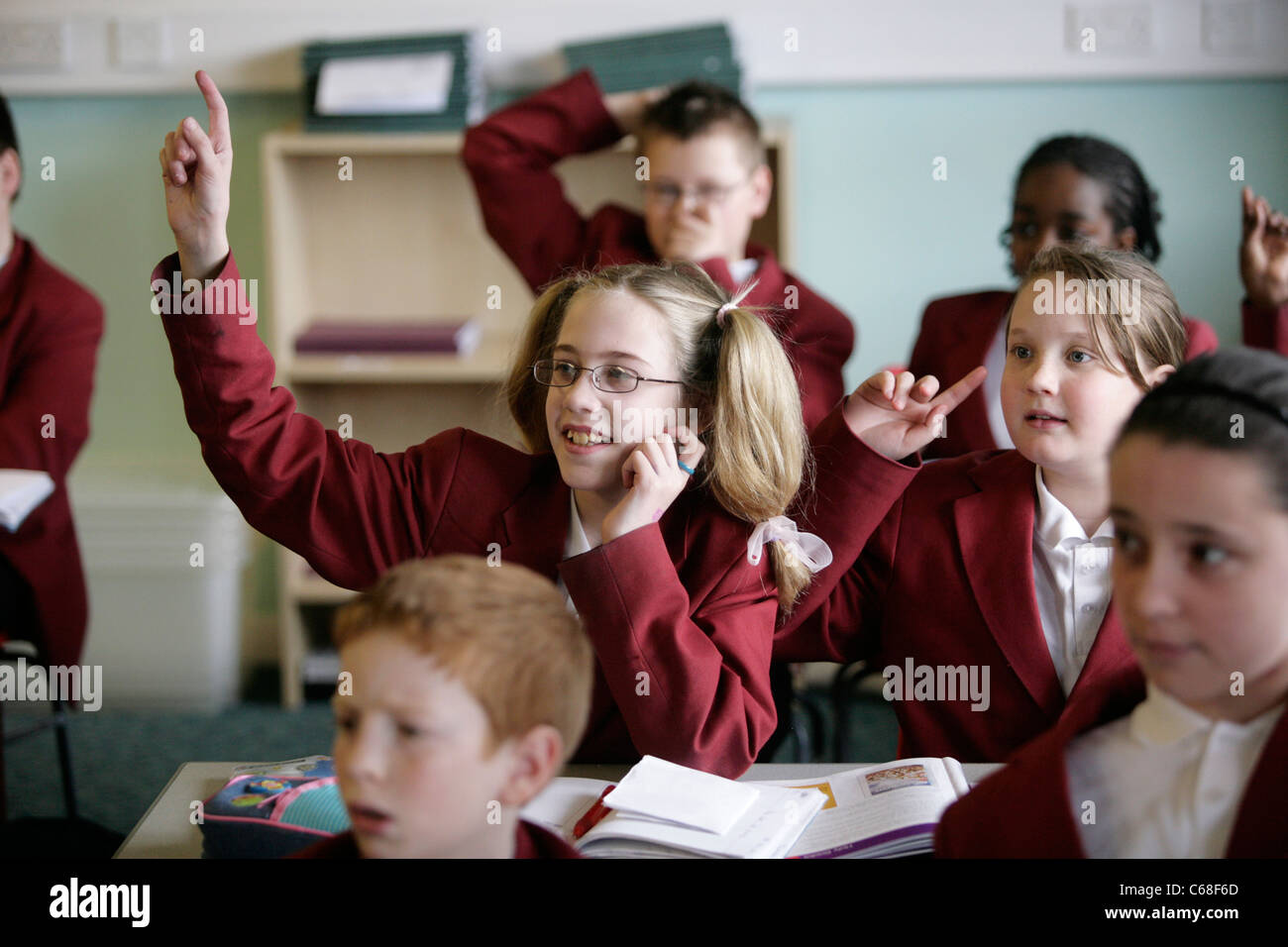 A pupil in a secondary school in the UK puts her hand up during a lesson to answer a question. - Stock Image
