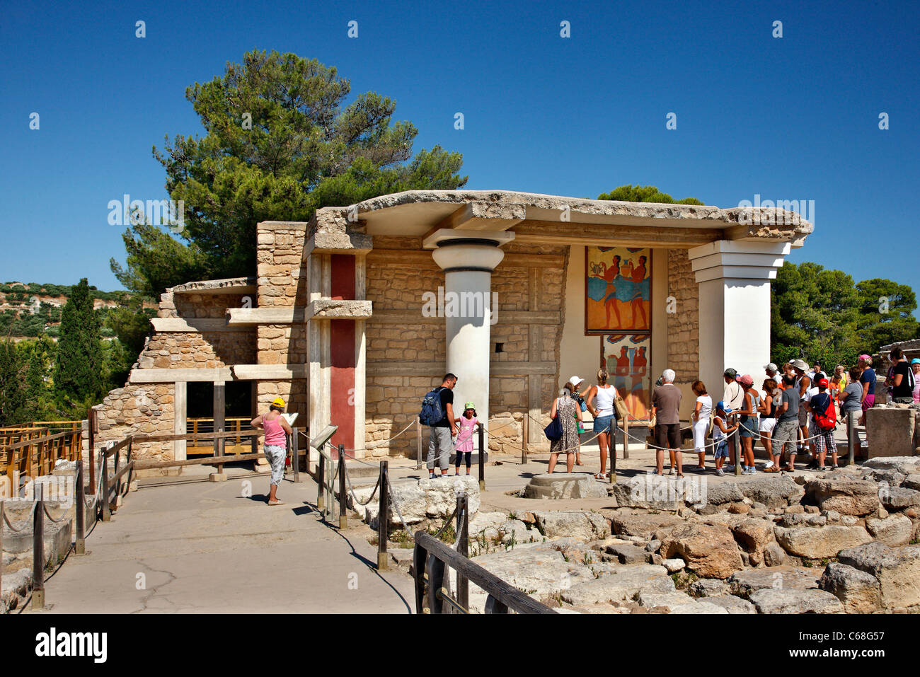 A group of tourists watching the 'Procession' fresco at the Minoan Palace of Knossos - Stock Image