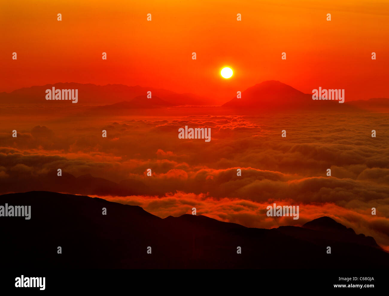 Sun setting above a sea of clouds. Photo taken from mount Kofinas the highest peak of Asterousia mountain range, Stock Photo