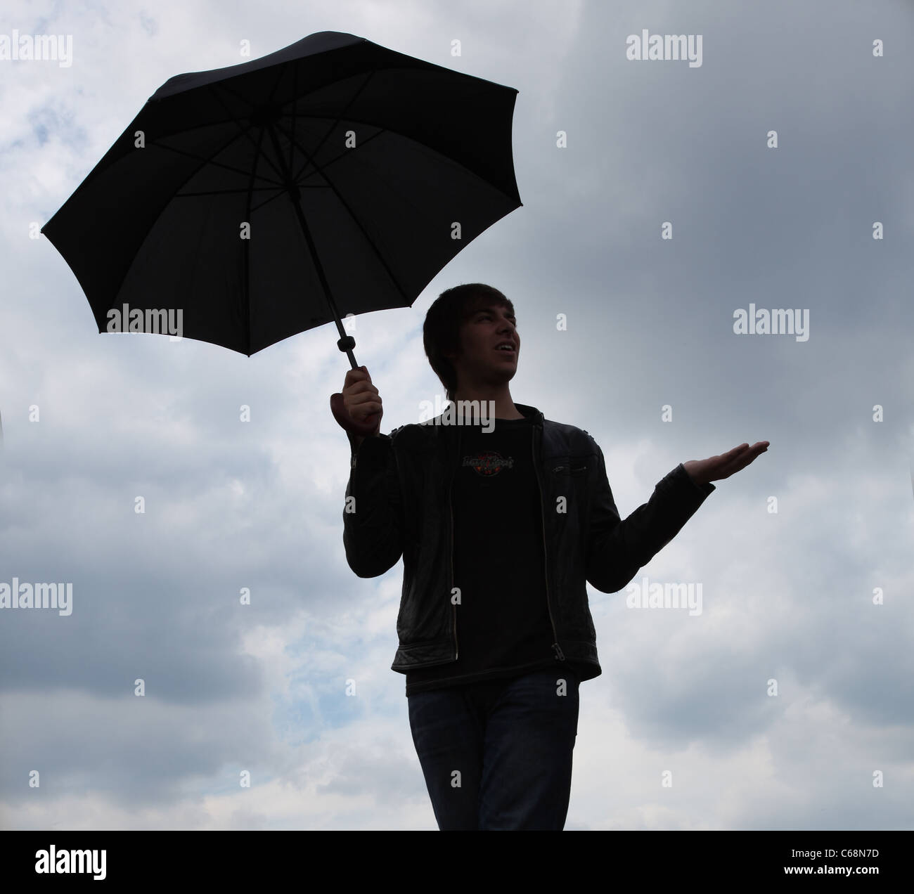 Man standing against a cloudy sky, hand out checking for rain, holding an umbrella. - Stock Image