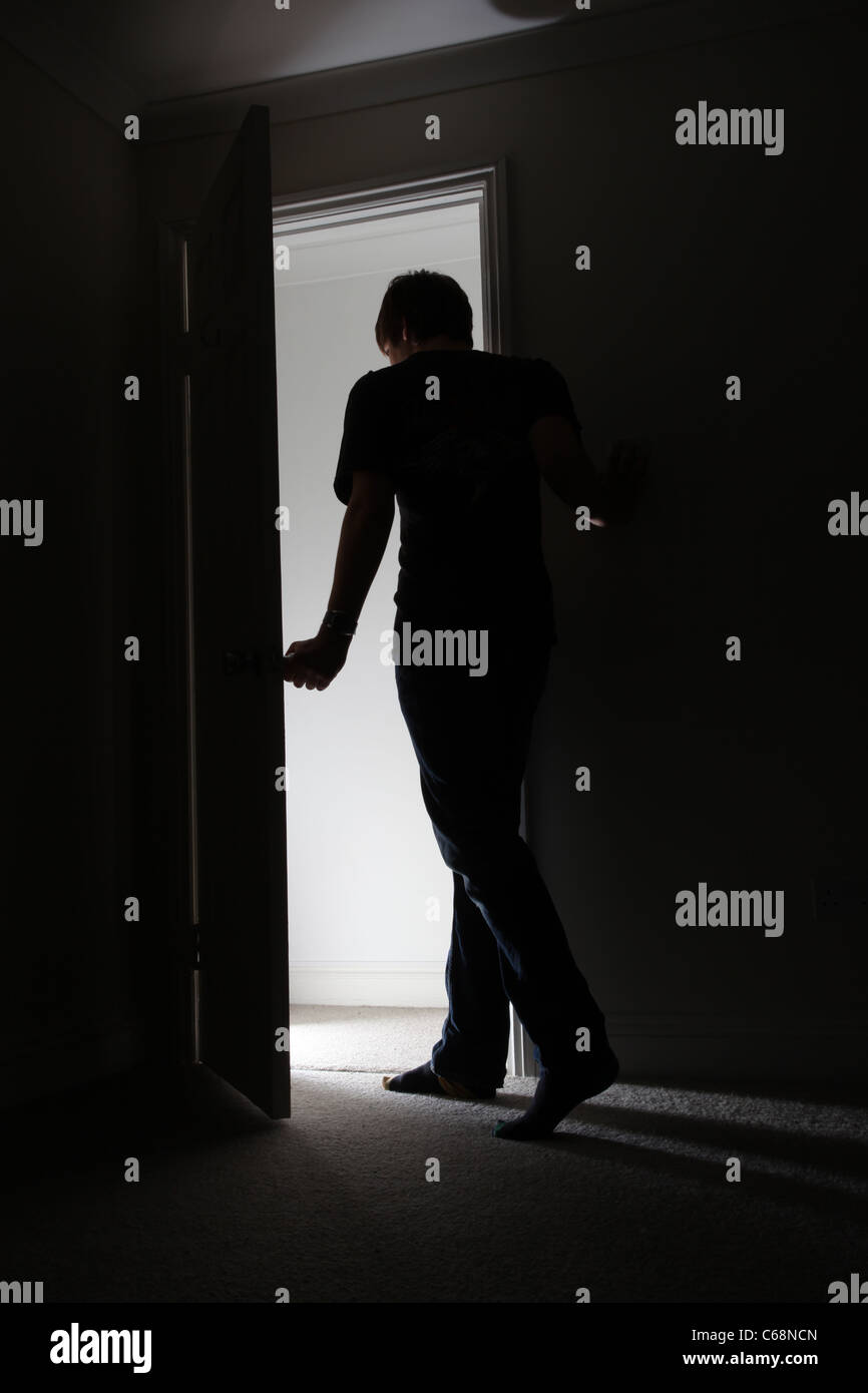 Silhouette Of A Man Leaving A Dark Room Stock Photo