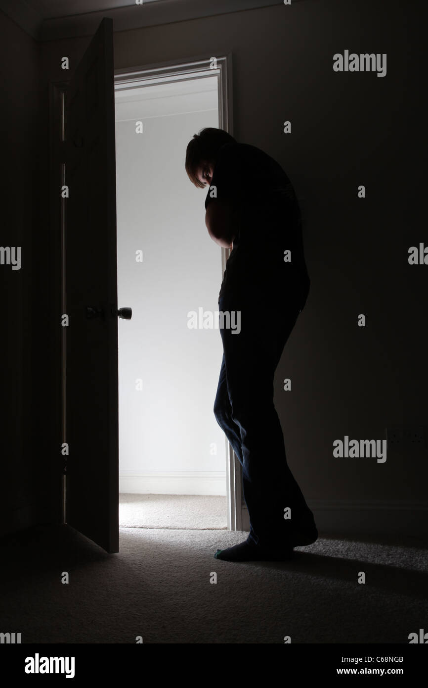 Man standing by an open door head down light coming from the hallway. - Stock Image