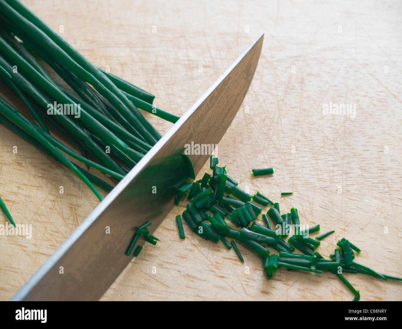 Schnittlauch wird auf einem Schneidbrett geschnitten | Chives is cutting on a cutting board - Stock Image