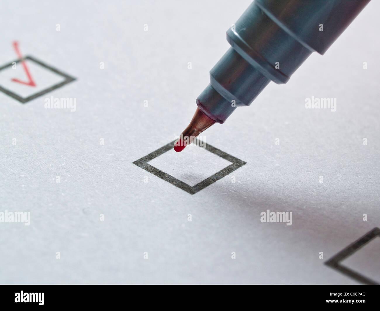 ein roter Stift über einem Kästchen, in einer Liste | a red pen over a small box in a list Stock Photo