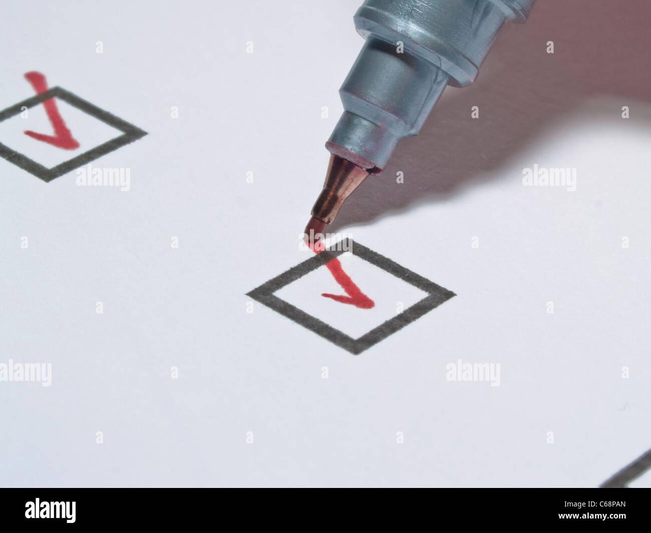 ein roter Stift hakt eine Kästchen in einer Liste ab   a red pin makes a check in a small box in a list Stock Photo