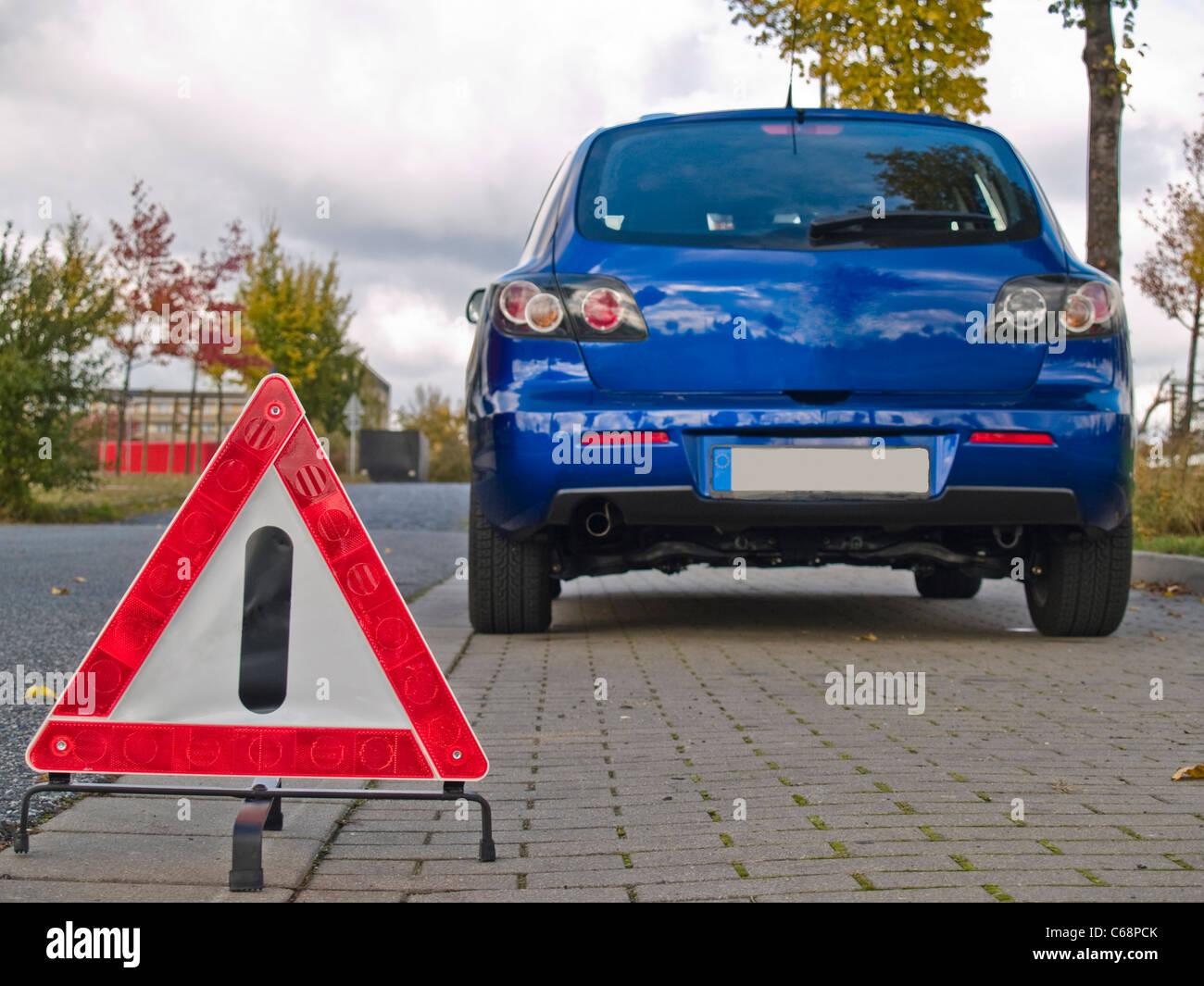 ein Warndreieck, davor steht ein blaues Auto | a warning triangle, in front is a blue car Stock Photo