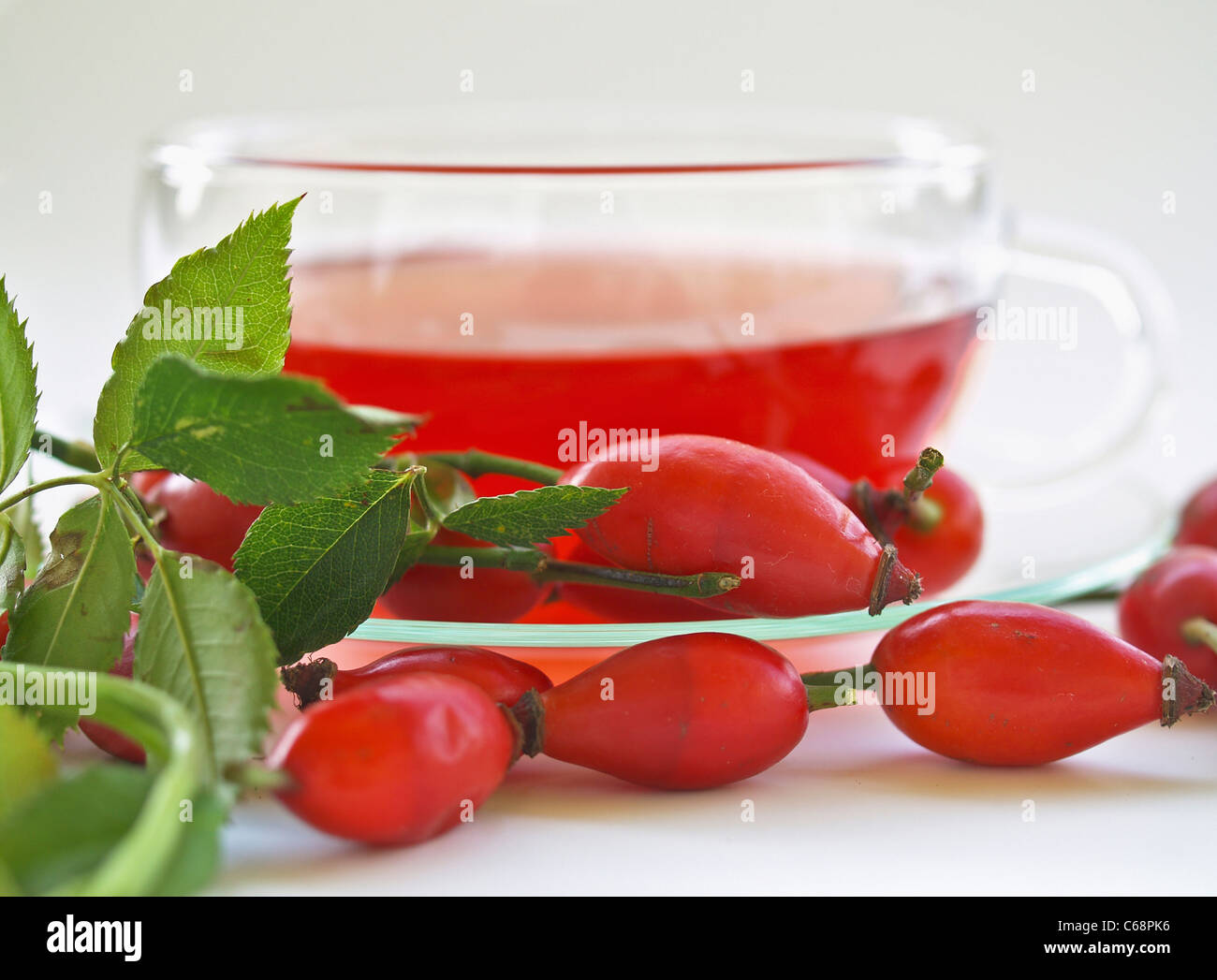 a glass cup with rose hip tea, in front are rose hip Stock Photo
