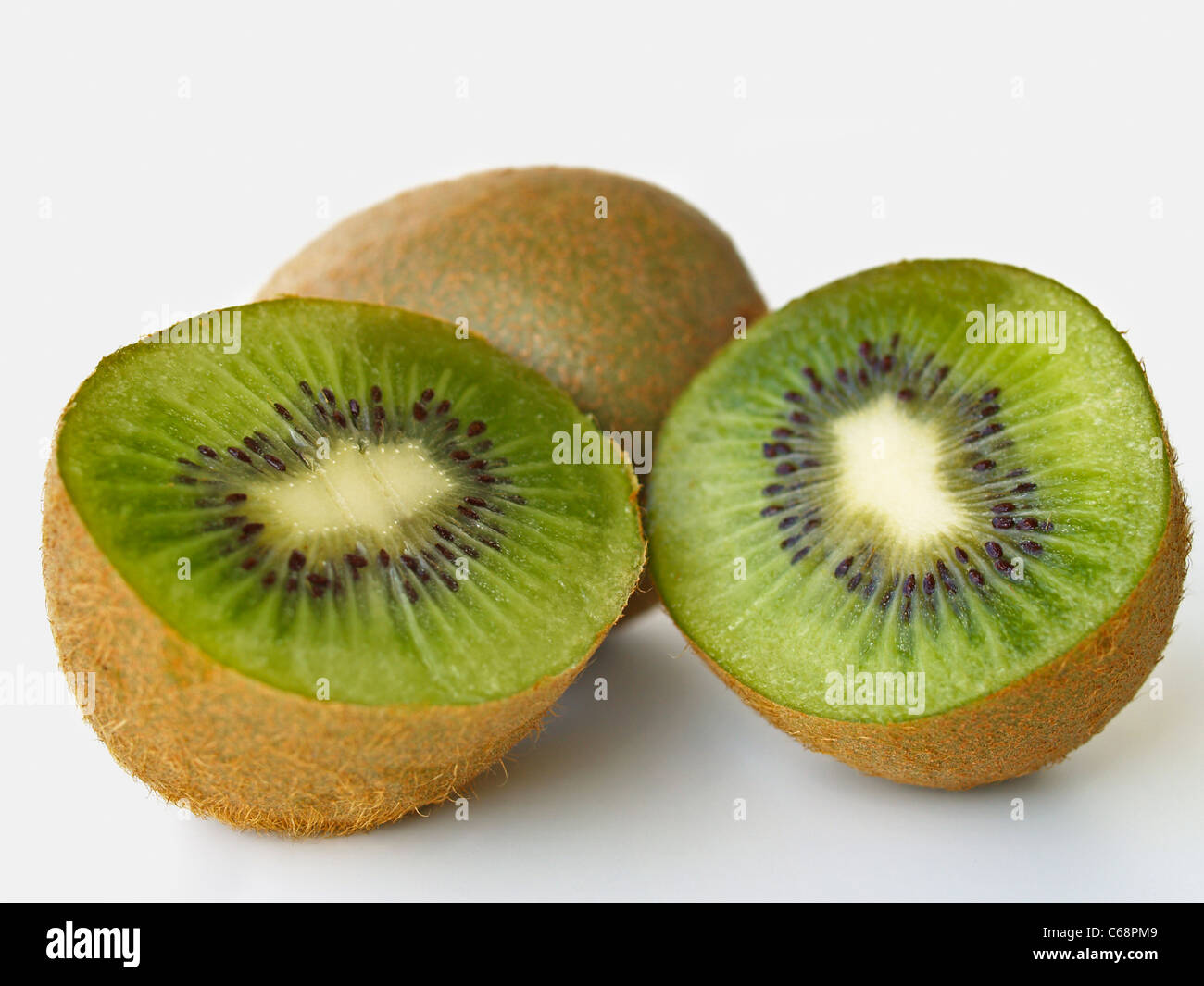 Detail photo of Kiwi fruits, in front is a sliced Kiwi fruit - Stock Image