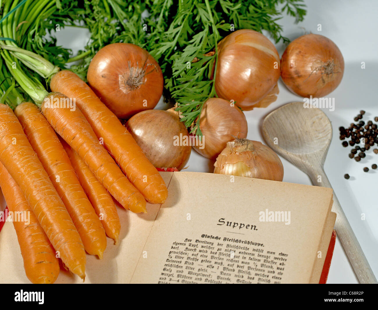 an old German cookbook side by side with carrots, onions and peppercorns and a wooden spoon - Stock Image