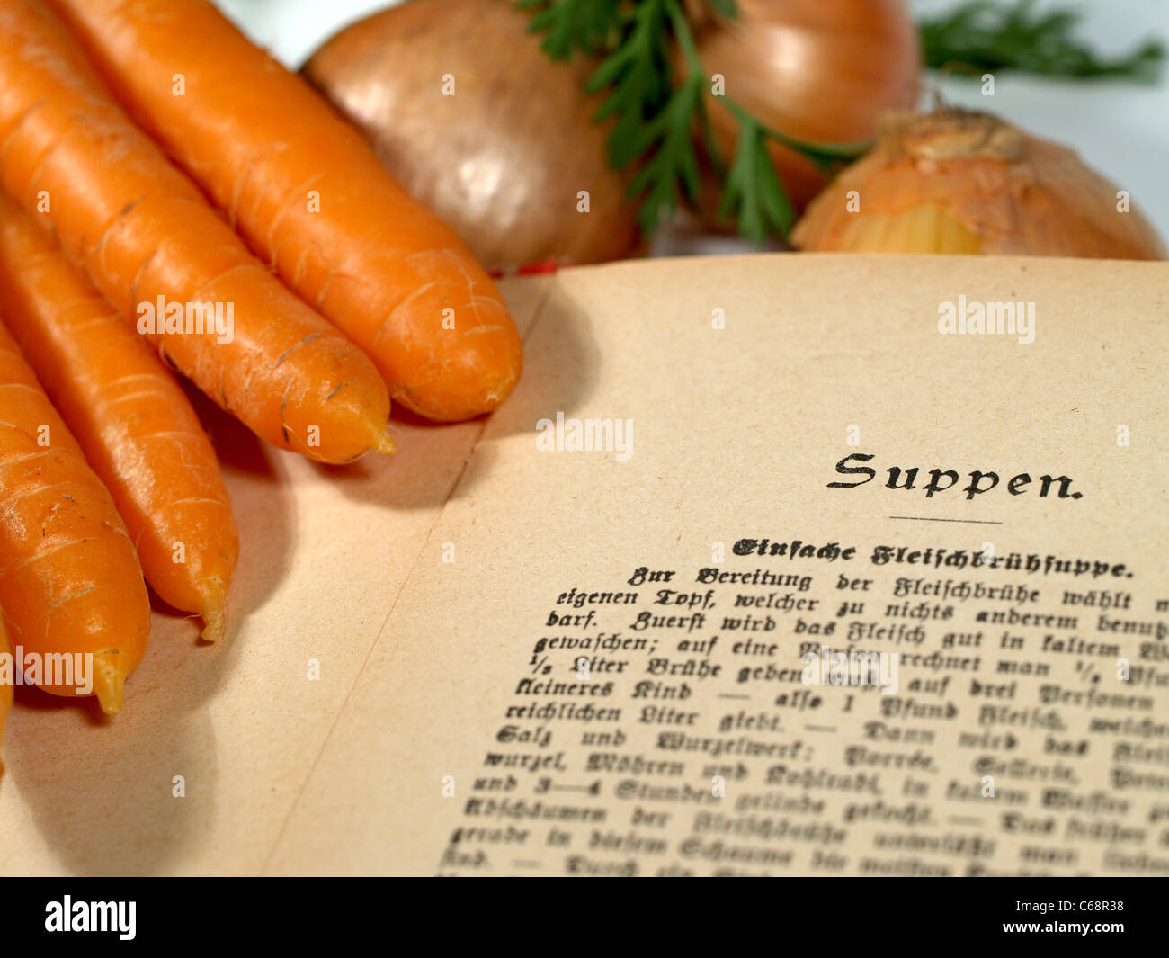 an old German cookbook side by side with carrots and onions - Stock Image