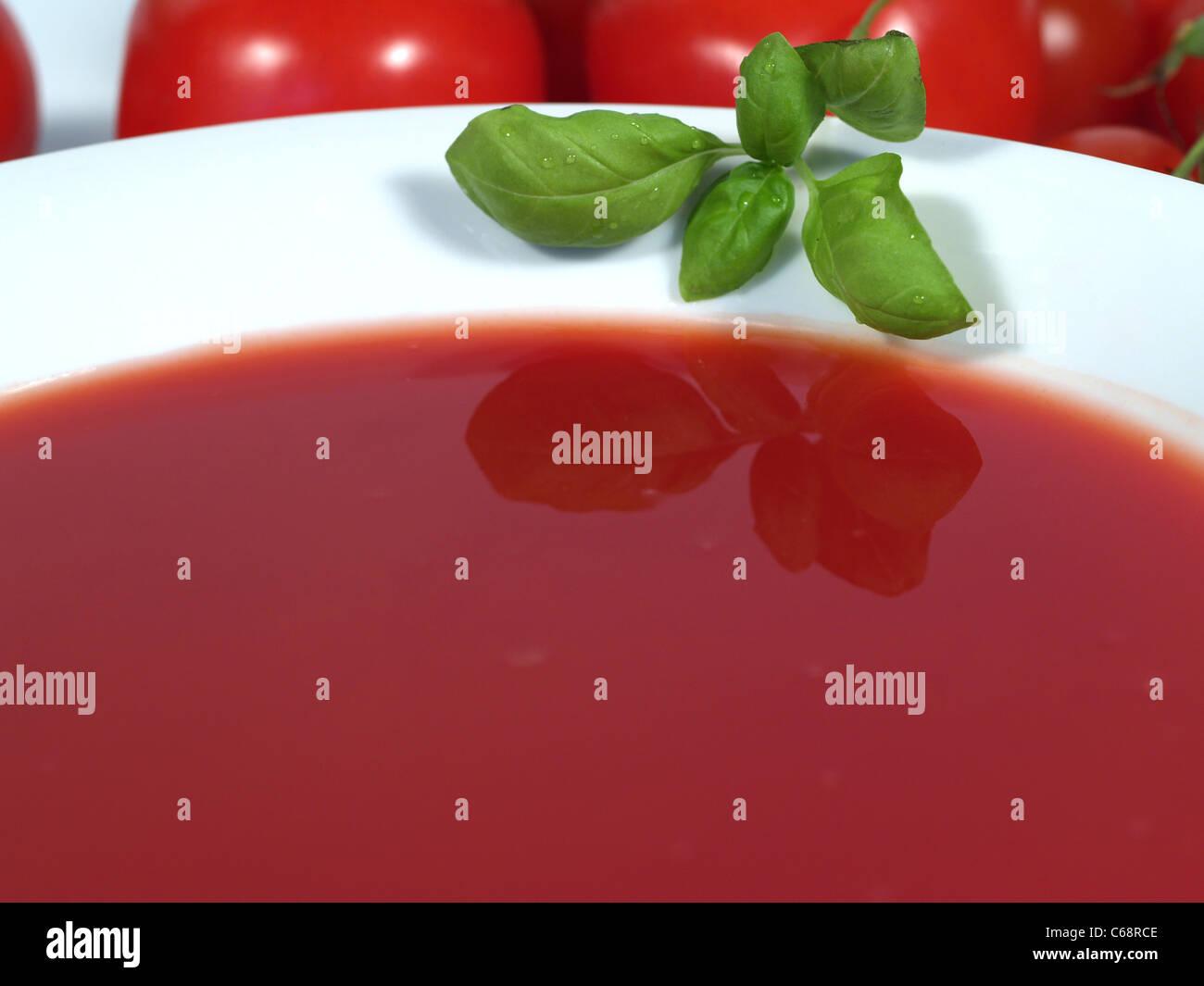Teller mit Tomatensuppe und einem Basilikumblatt. dahinter Tomaten | Plate with tomato soup and a basil leaf, tomatoes Stock Photo