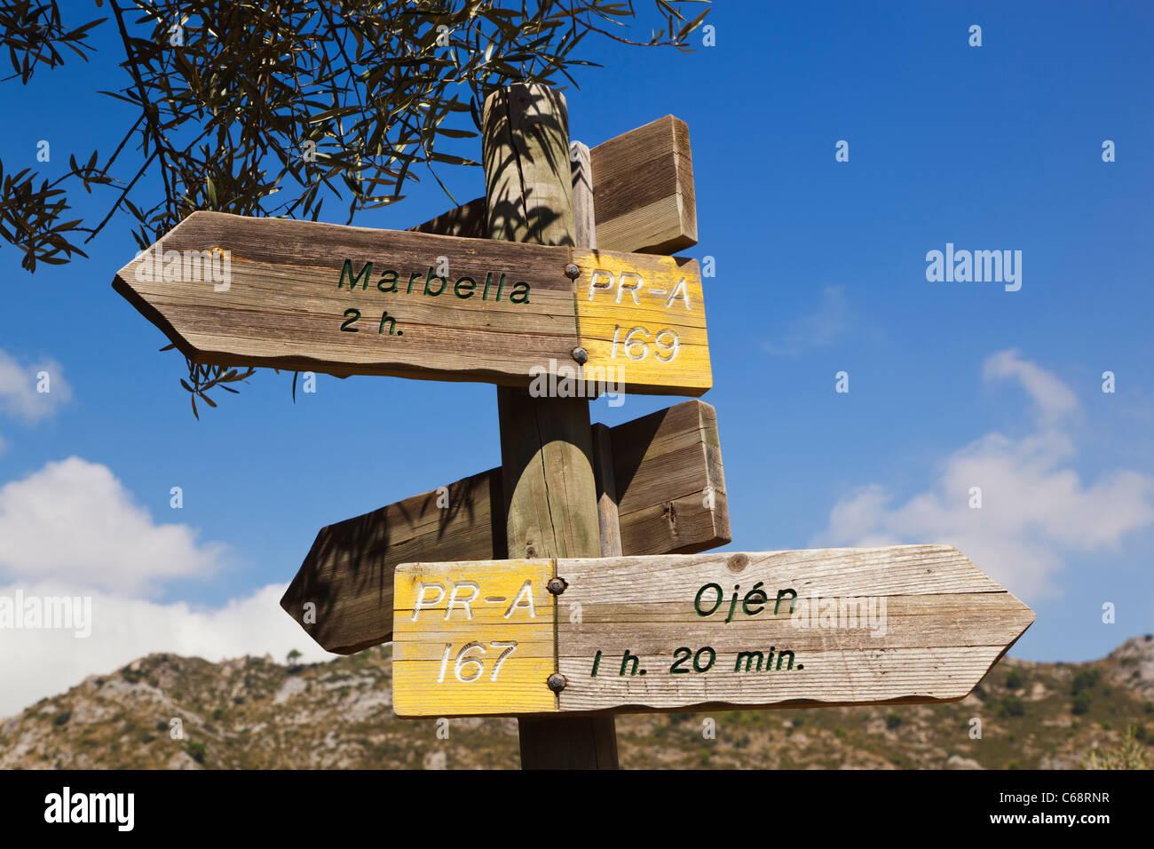 Signpost on walker's path in the Sierra Blanca de Ojen pointing to Ojen and Marbella. Near Ojen, Spain - Stock Image