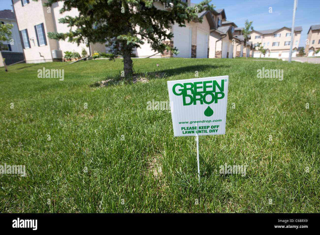 green drop sign to keep off the lawn until dry on managed condominium property Saskatoon Saskatchewan Canada - Stock Image