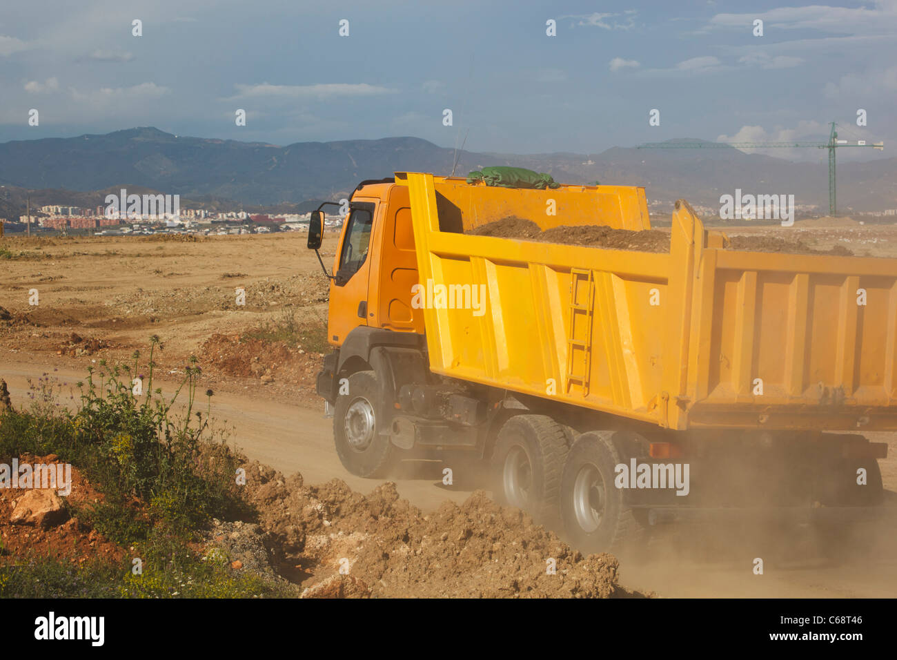 Dump truck laden with earth driving on construction site. - Stock Image