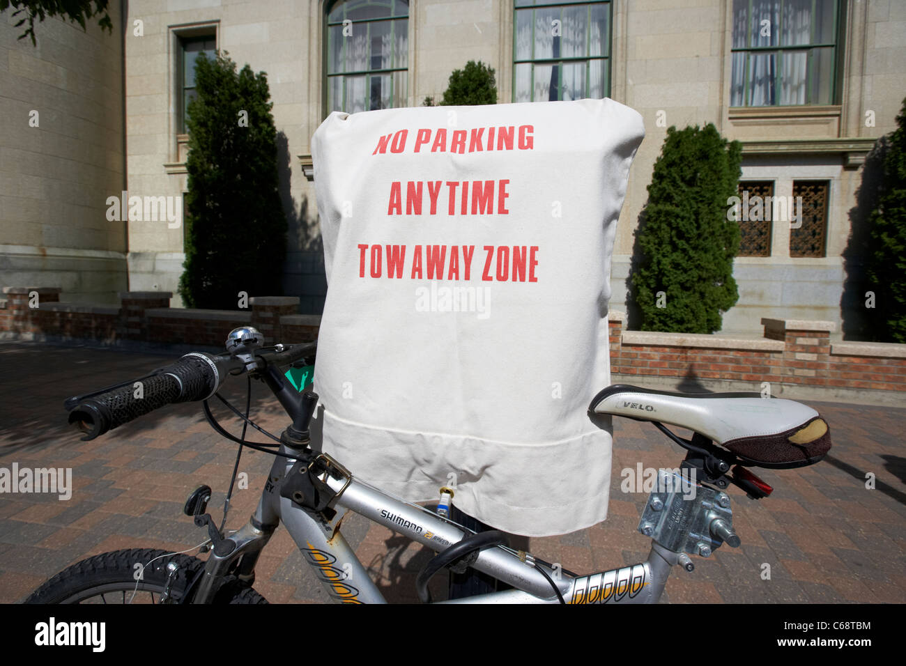 bike locked to no parking anytime tow away zone sign covering out of order parking meters Saskatoon Saskatchewan - Stock Image