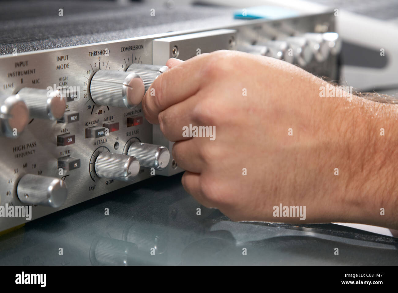 mans hand adjusting compression on avalon vacuum tube sound engineering equipment - Stock Image