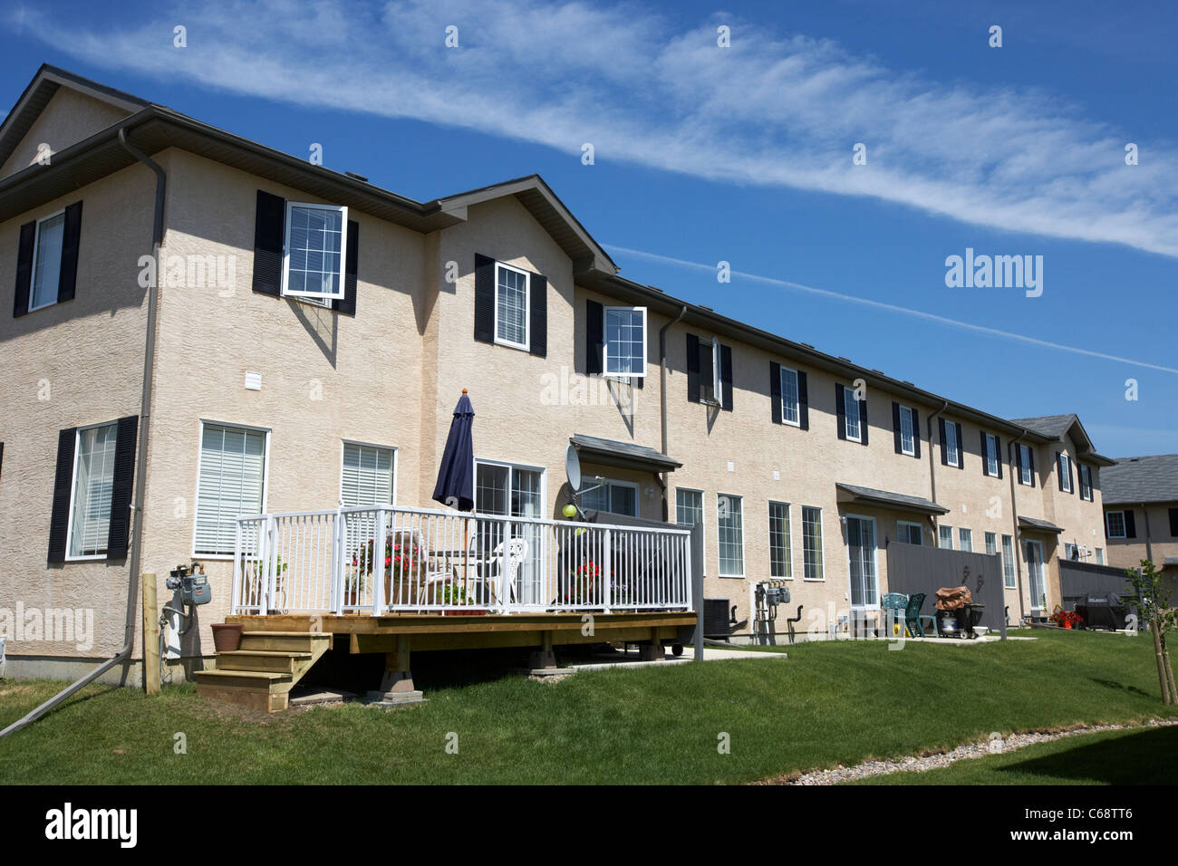 rear of row of townhouses starter homes some with decking on managed property Saskatoon Saskatchewan Canada - Stock Image