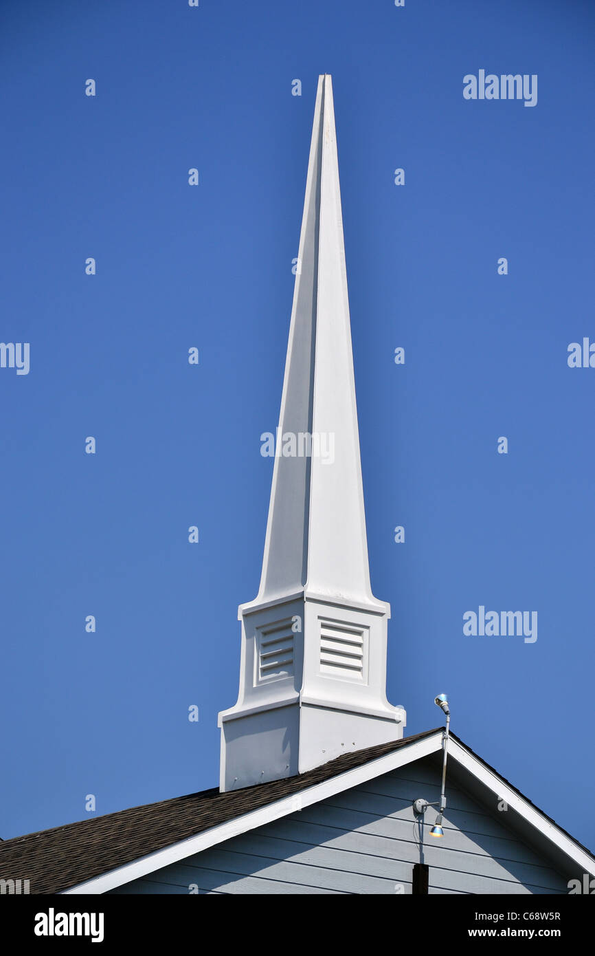 A view of a white church steeple on a blue sky background. - Stock Image