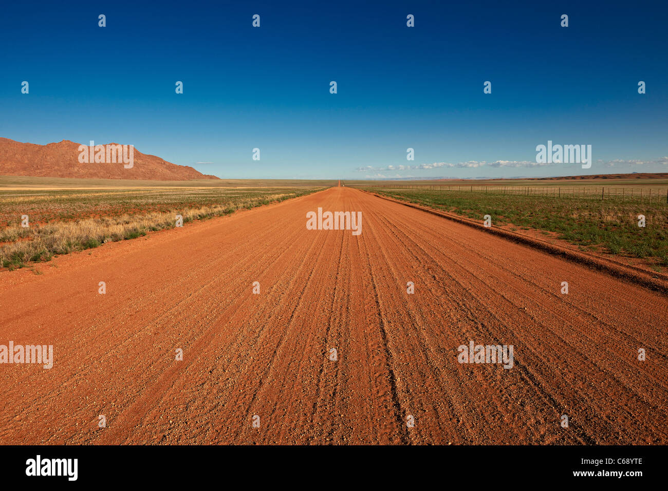 straight deserted gravel road in desert landscape, most beautiful secondary road of the world D707, Namibia, Africa Stock Photo