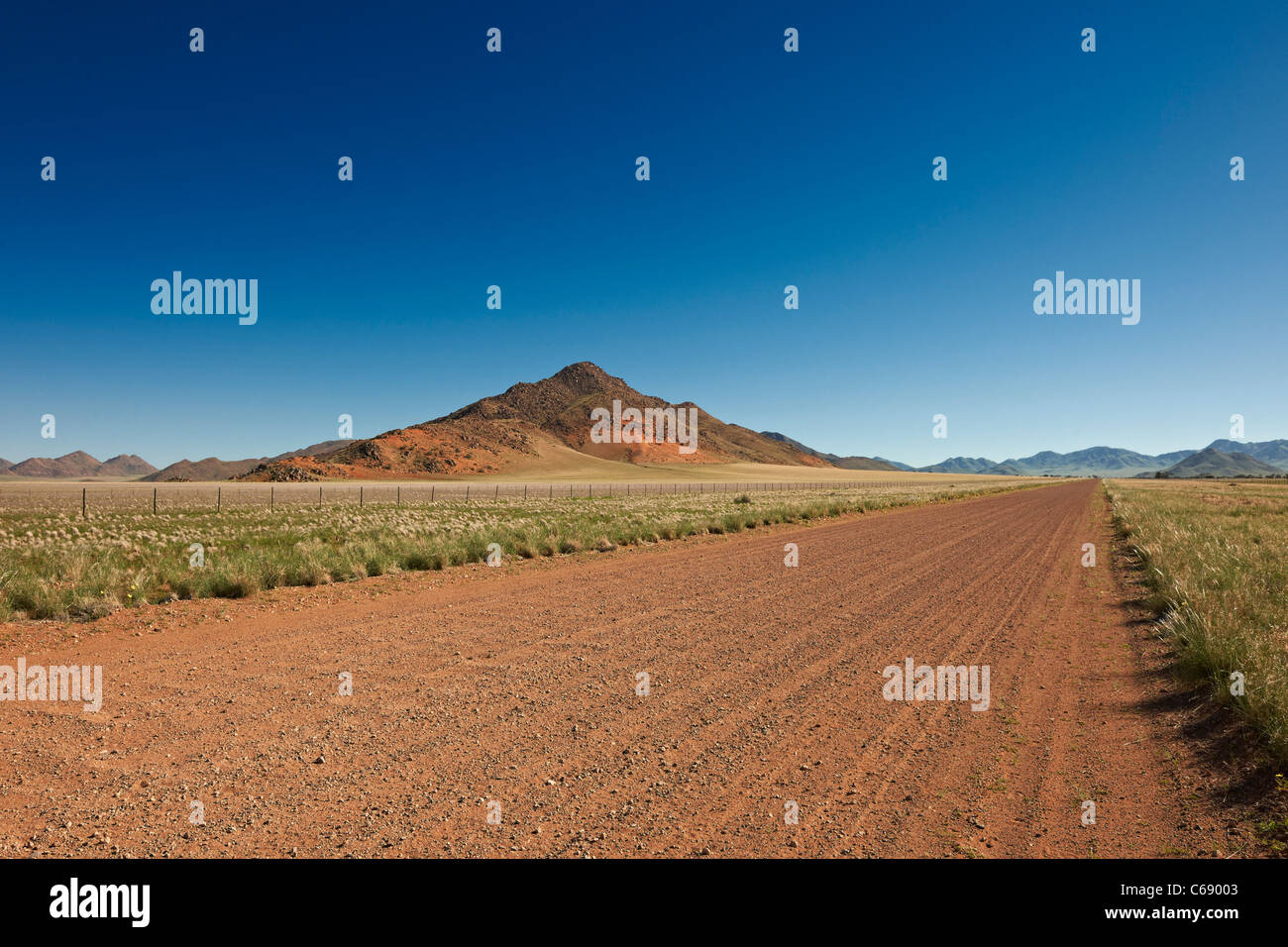straight deserted gravel road in desert landscape, most beautiful secondary road of the world D707, Namibia, Africa - Stock Image