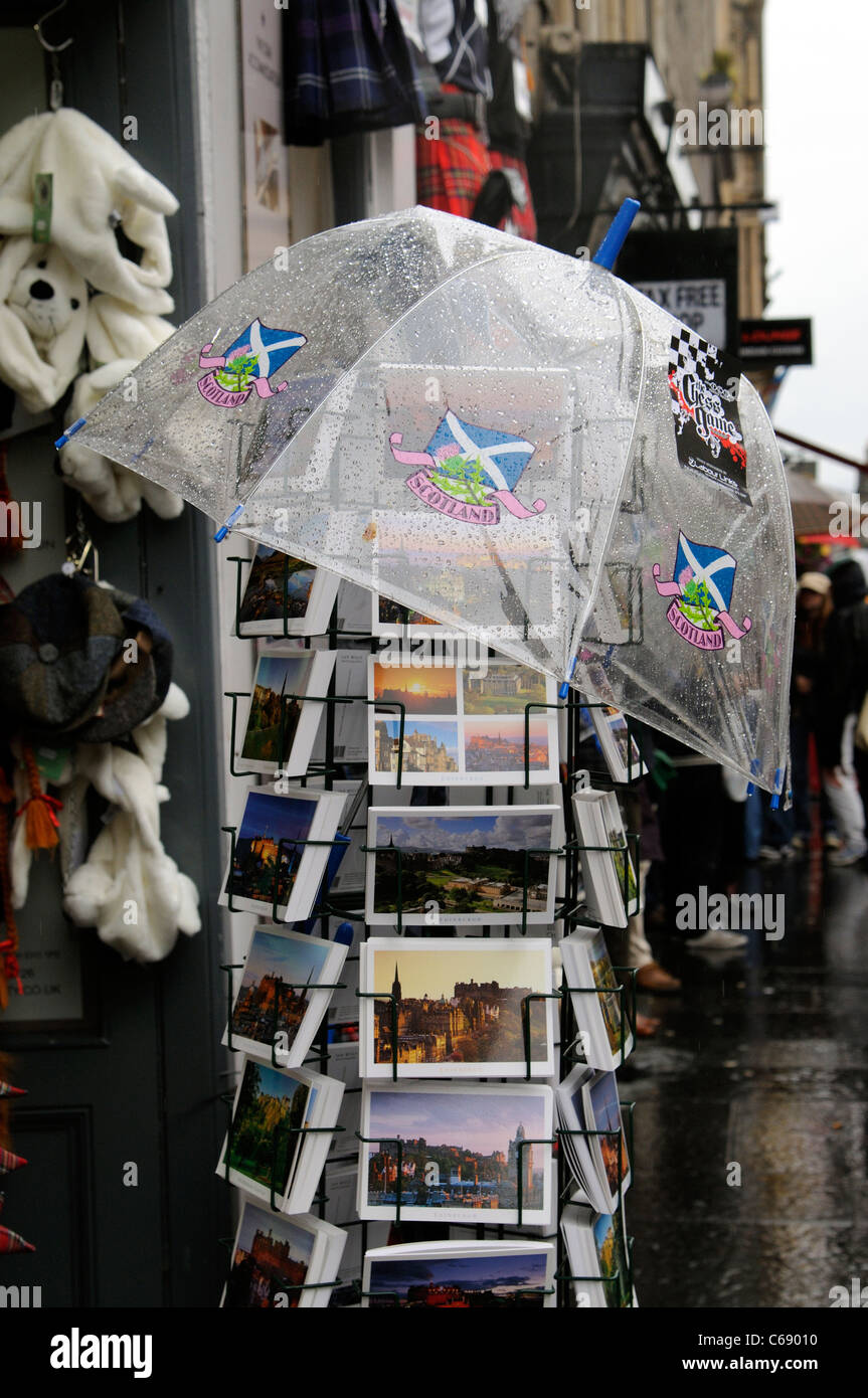 See through umbrella protecting stock of picture postcards on a rack during rain. Edinburgh Scotland - Stock Image