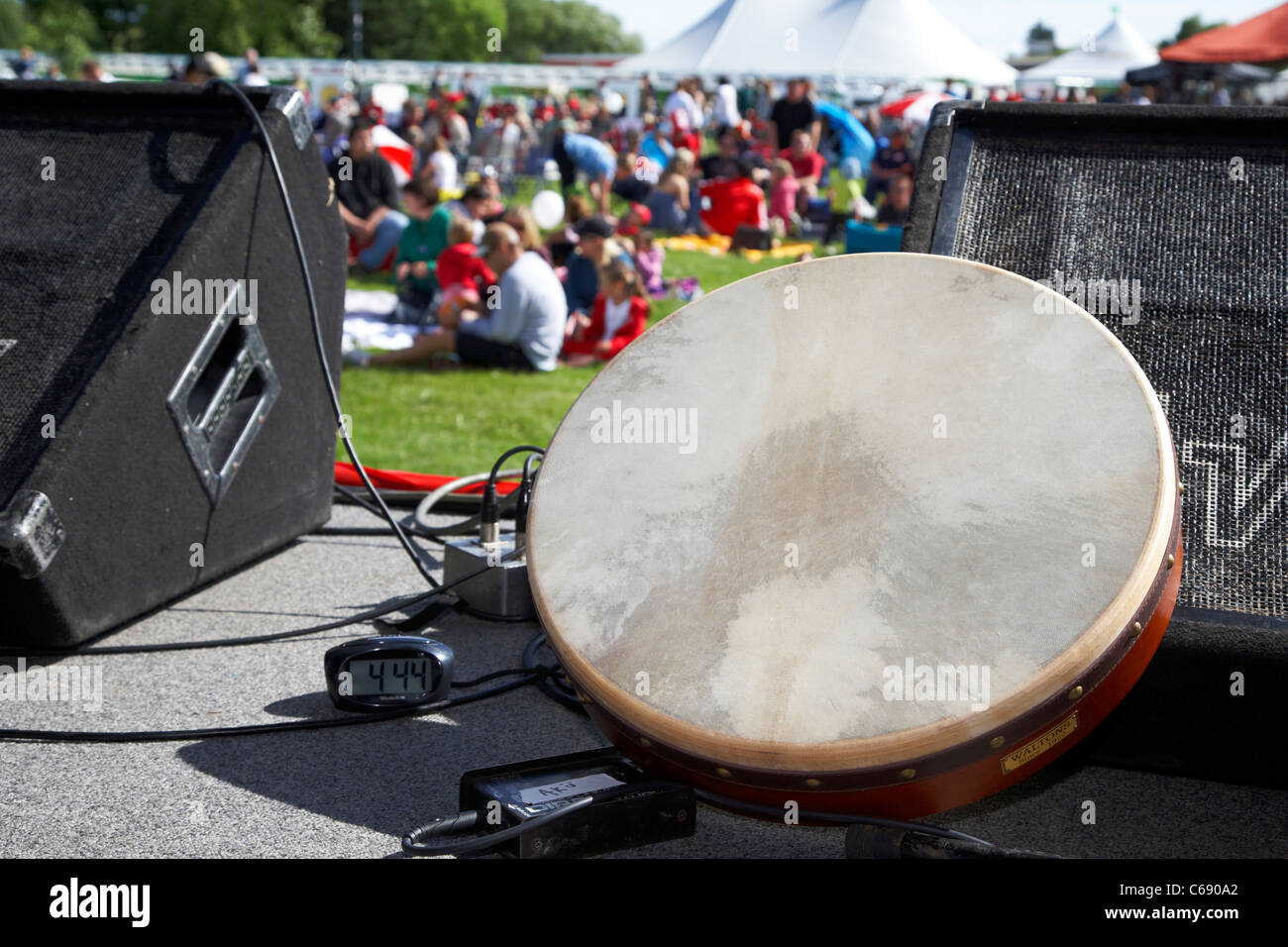 irish bodhran drum clock and monitor speakers on stage at a summer outdoor festival Saskatoon Saskatchewan Canada - Stock Image