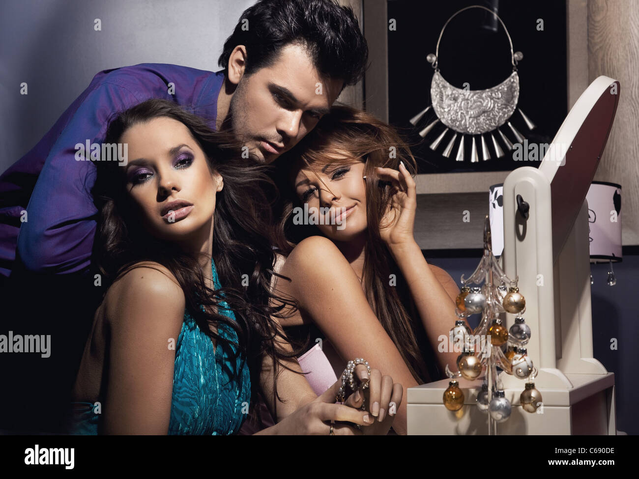 Two pretty girls and one handsome man posing - Stock Image