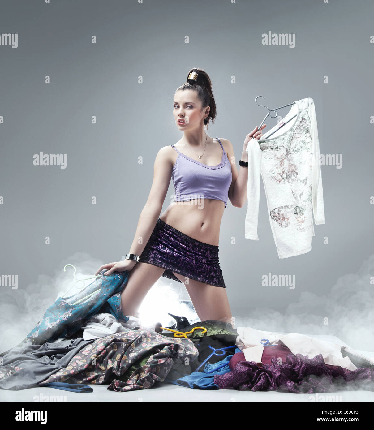 Portrait of pretty woman choosing new clothes and looking at camera - Stock Image
