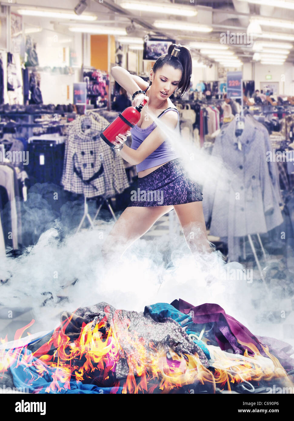 Nice girl irl is extinguishing the fire of clothes - Stock Image