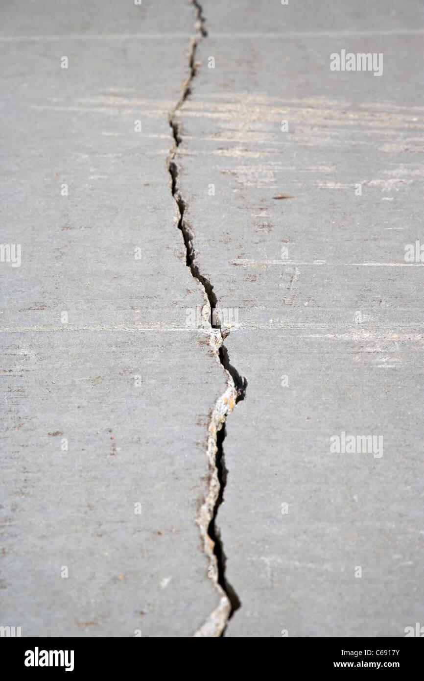 long crack along concrete footpath caused by bad cold weather Saskatoon Saskatchewan Canada - Stock Image