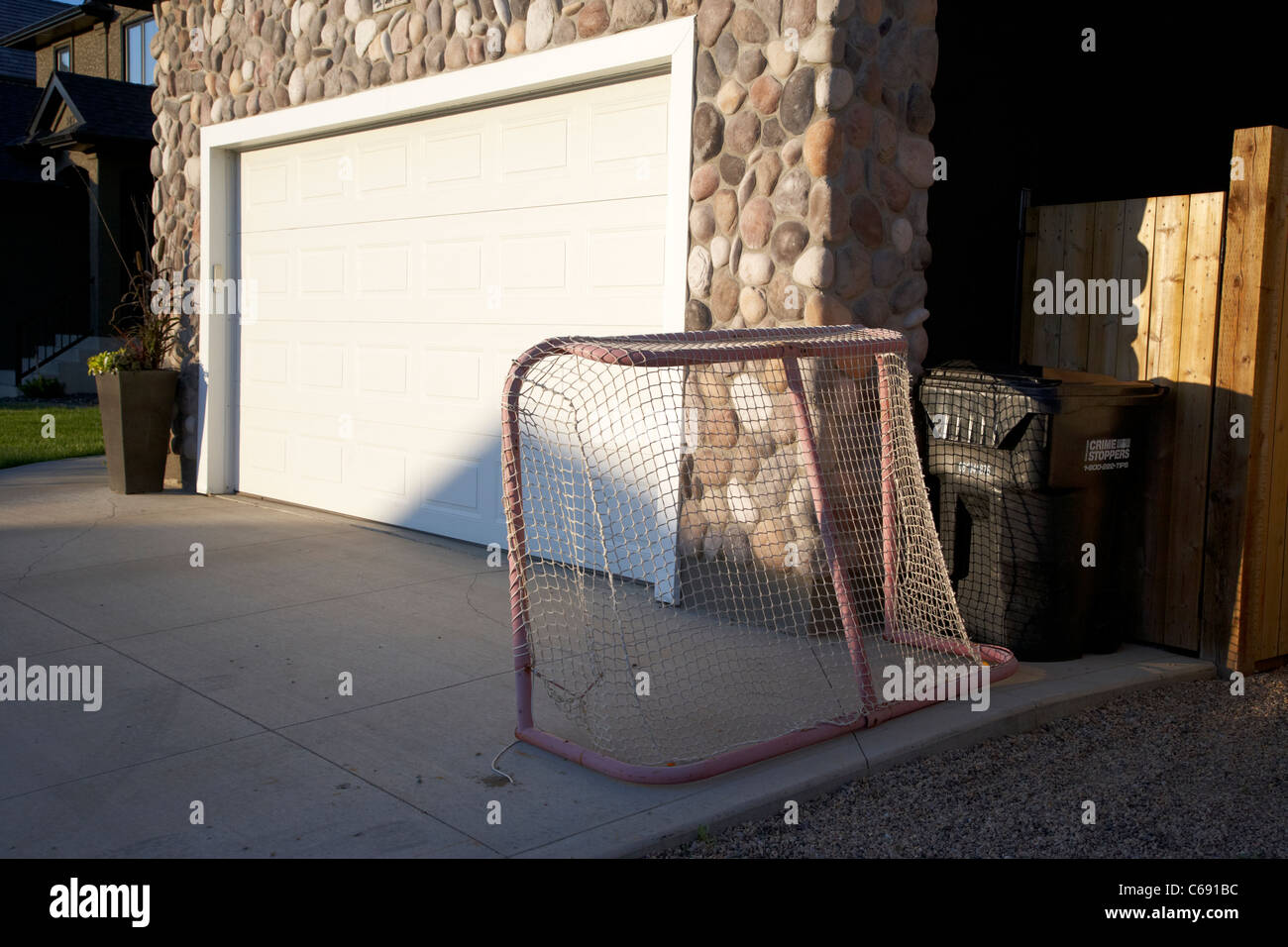 ice hockey goal on house driveway in Saskatoon Saskatchewan Canada - Stock Image
