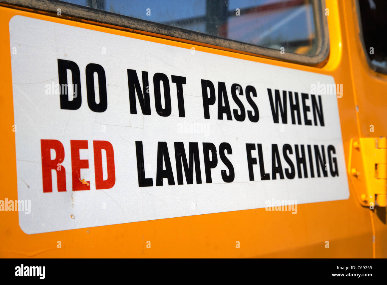 do not pass when red lamps flashing sign on the back of a yellow school bus Saskatoon Saskatchewan Canada - Stock Image