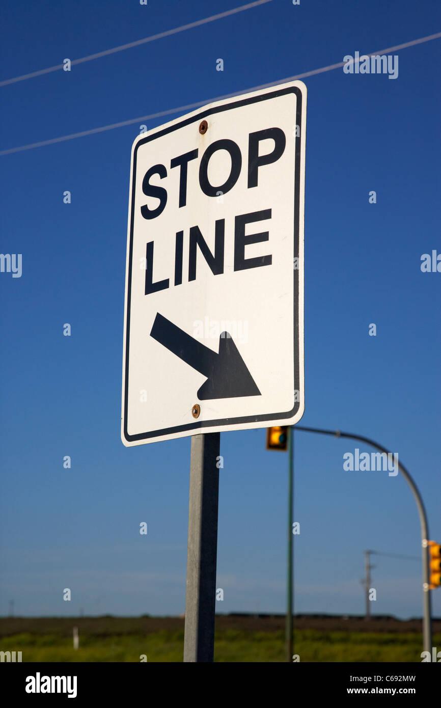 stop line sign at road junction intersection Saskatoon Saskatchewan Canada - Stock Image