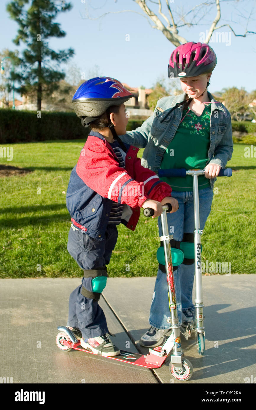 Wearing jacket Young girl and pre-K Hispanic boy on scooters at park child helping another  MR © Myrleen Pearson Stock Photo