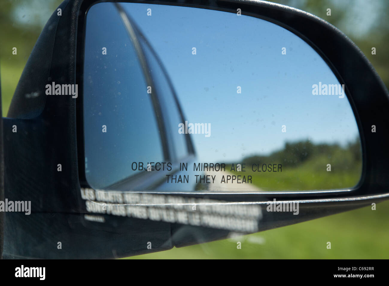 objects in mirror are closer than they appear in car side mirror on highway Canada - Stock Image