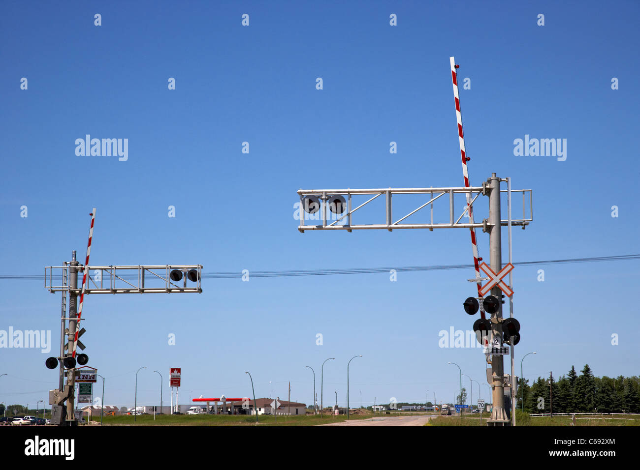 high level railroad crossing lights and barriers against blue sky Saskatchewan Canada - Stock Image
