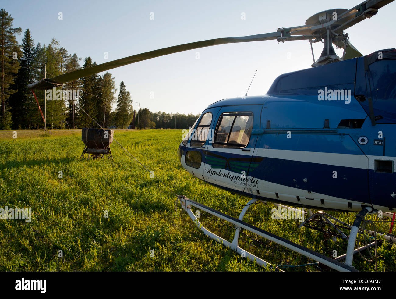 Helicopter , used for fertilizing forests , has  landed to a field , ferttilizer spreader bucket / apparatus at - Stock Image