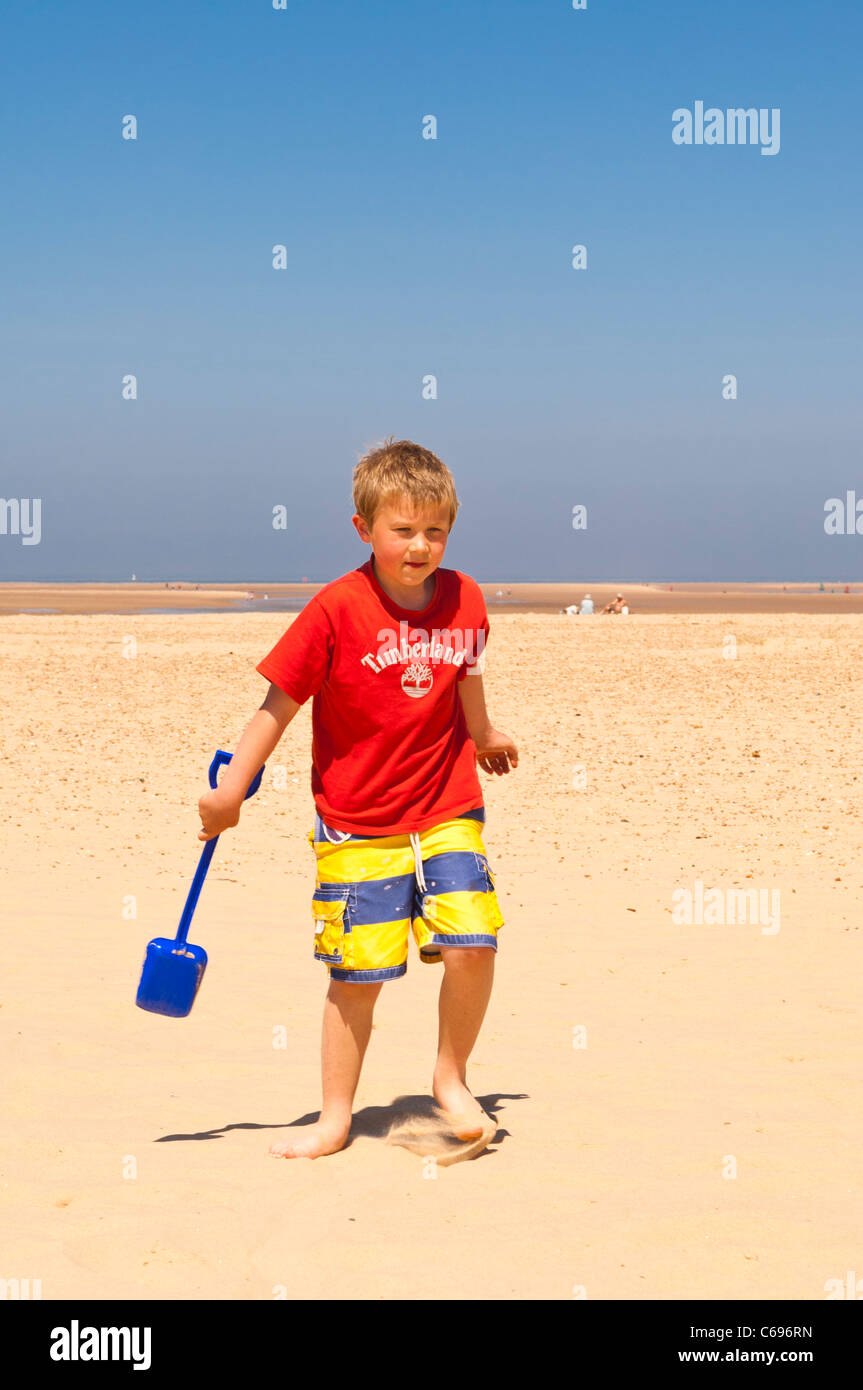 A seven year old boy playing on the beach at Wells-next-the-sea , Norfolk , England , Britain , Uk - Stock Image