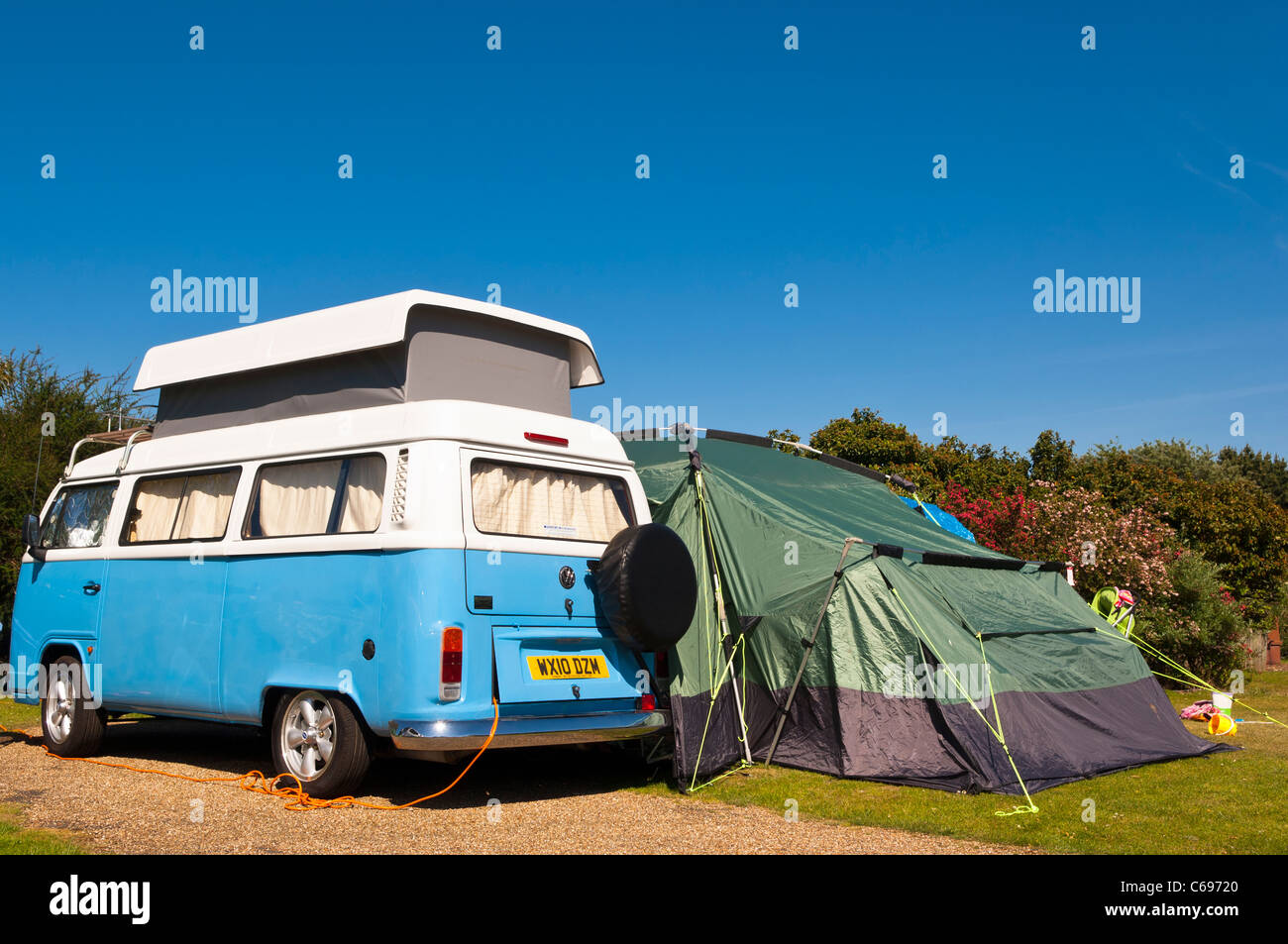 A VW camper set up camp along with tent on a Uk camping site - Stock Image