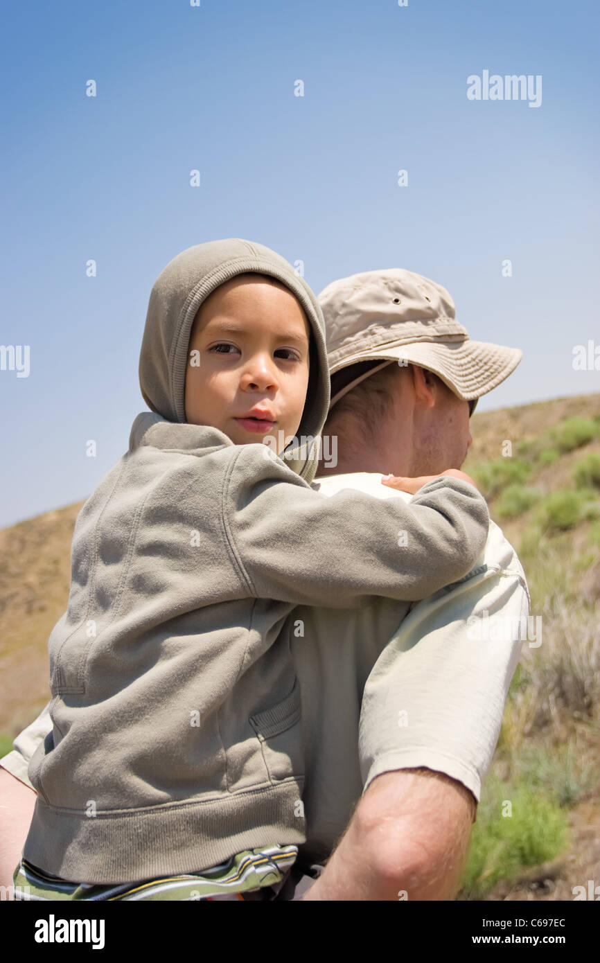A young boy riding piggy back with father hiking up a trail - Stock Image