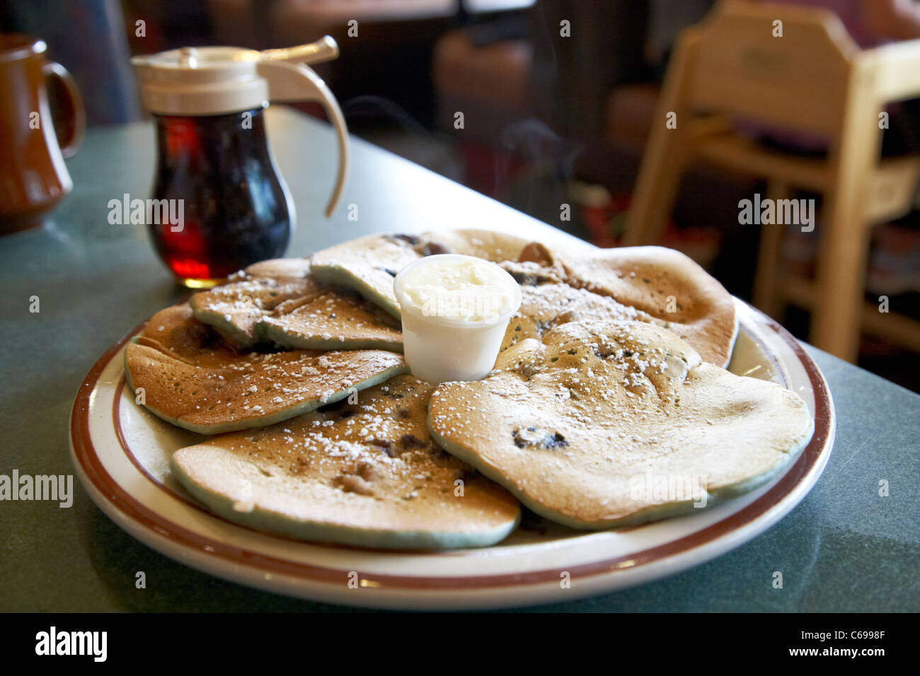 plate of freshly made blueberry pancakes whipped butter and maple syrup in a cafe in canada - Stock Image