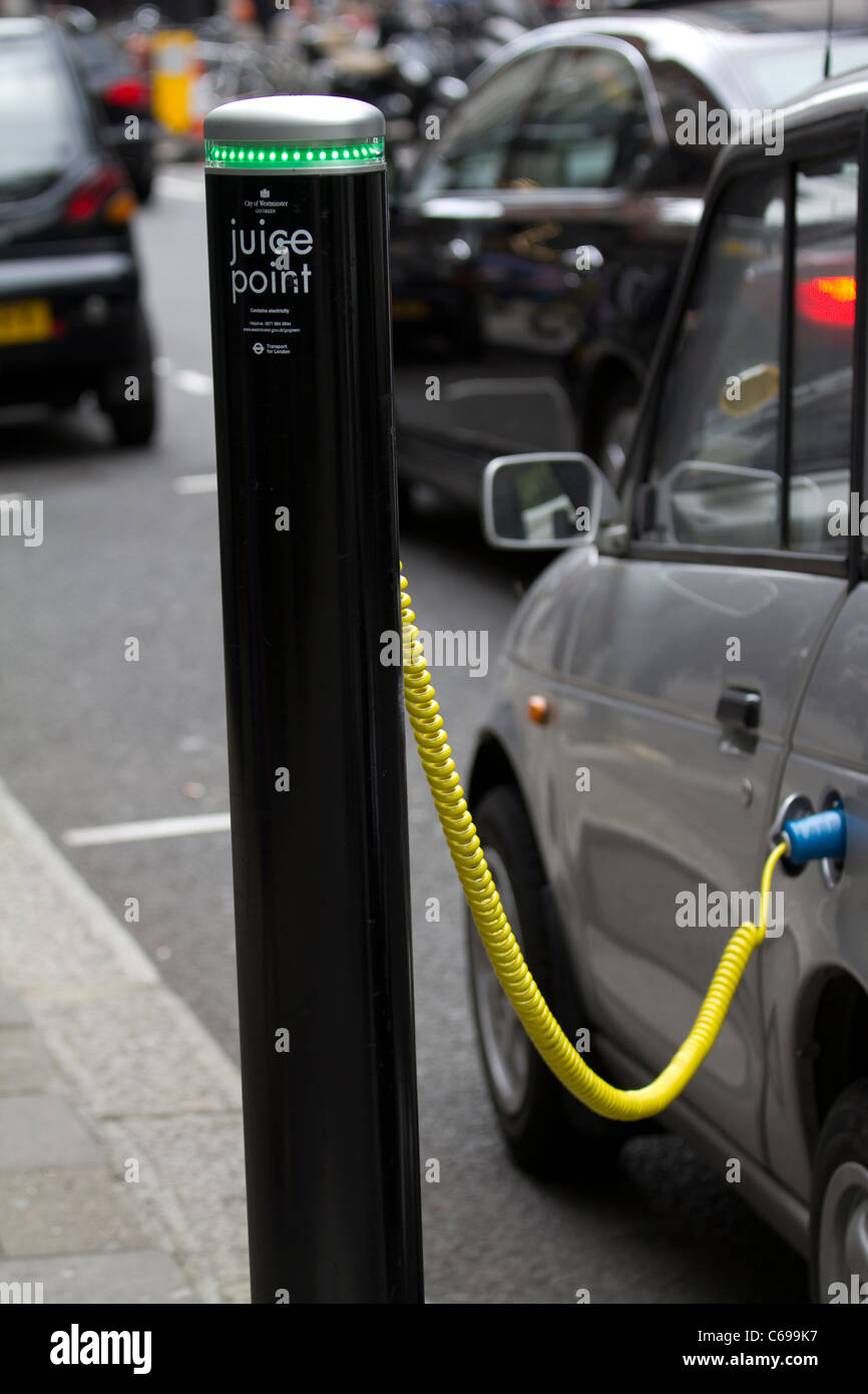 electric car vehicle juice point car charging in london while parked - Stock Image