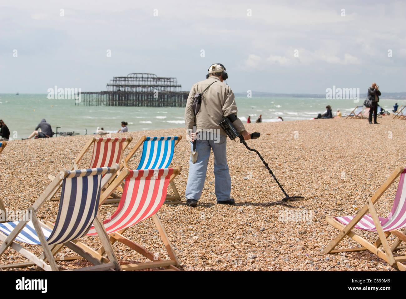 Brighton Sussex metal detector, man searching for coins with a metal detector on brighton beach - Stock Image