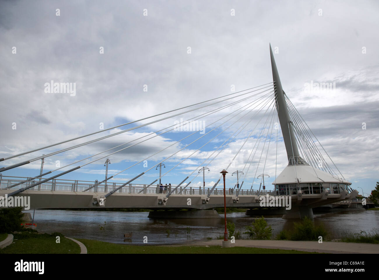 esplanade riel bridge on an overcast day with the red river flooding the forks Winnipeg Manitoba Canada - Stock Image