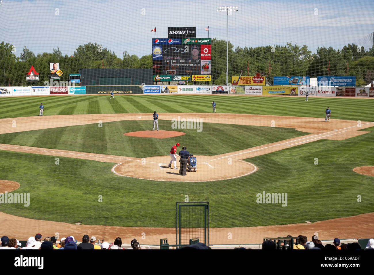 game ongoing behind safety net at shaw park baseball stadium formerly canwest home to the winnipeg goldeyes Winnipeg - Stock Image