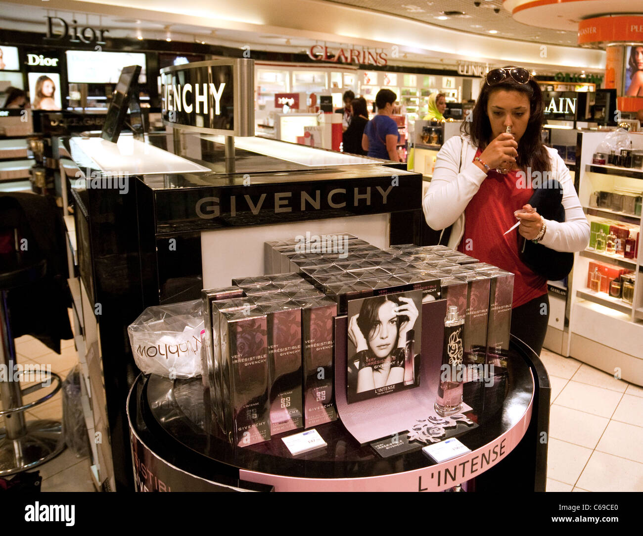 A teenage girl trying Givenchy perfume, the duty free store, Terminal 3, Heathrow airport London UK - Stock Image